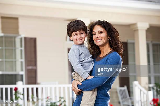 Little boy with mother in front of house