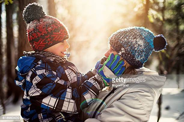 Little boy with mother on in winter forest