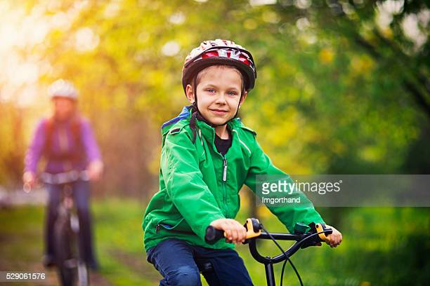 Little boy with mother riding bicycles in beautiful nature