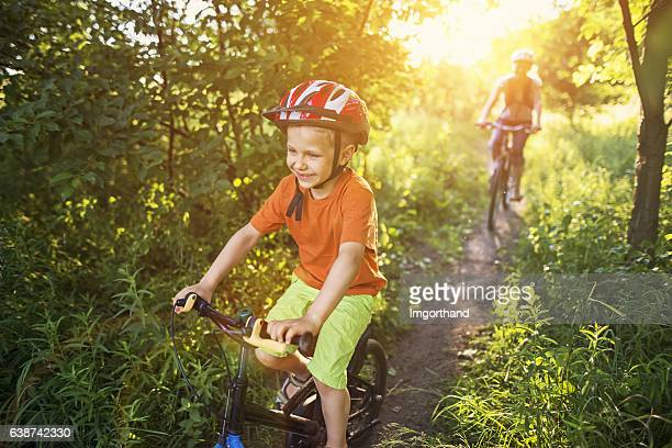 Little boy with mother riding bicycles on beautiful forest path