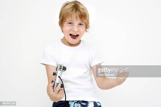 Little boy (10-11) with paddle, rejoicing, clenching fist
