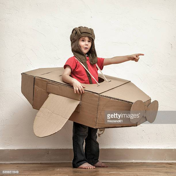 Little boy with pilot hat and cardboard box aeroplane showing at something
