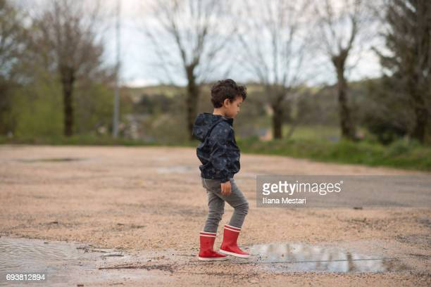 A little boy with rain boots playing with paddles