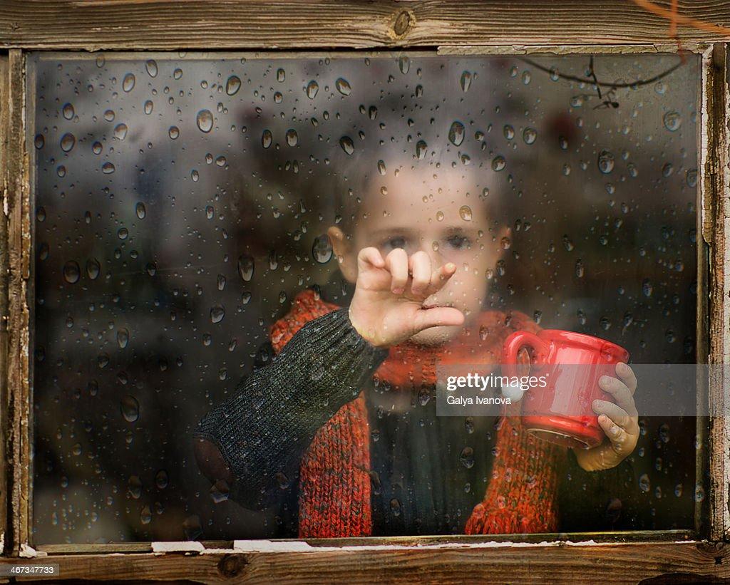 little boy with scarf behind rainy window : Stock Photo