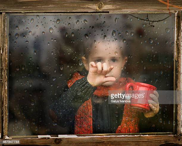 little boy with scarf behind rainy window