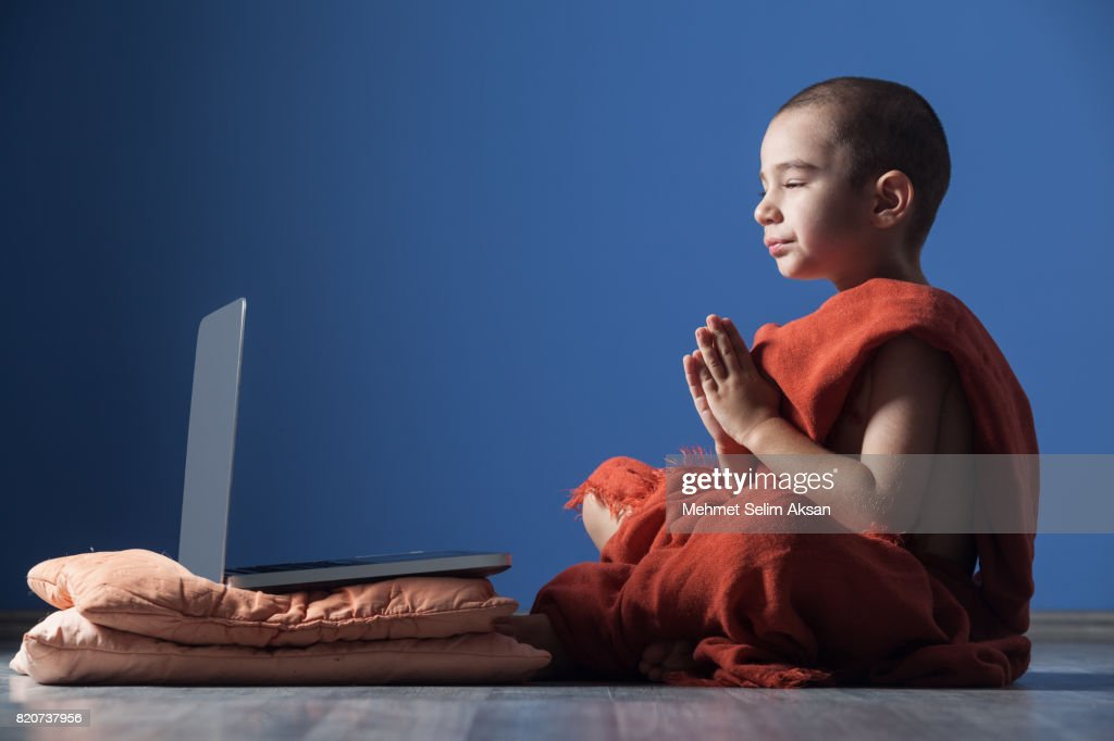 Little Boy With Shaved Head Wearing Orange Monk Robe And Meditating In Front Of Computer : Stock Photo