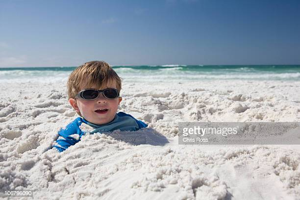 A little boy with sunglasses is buried in the sand up to his head with blue sky and ocean in the background.