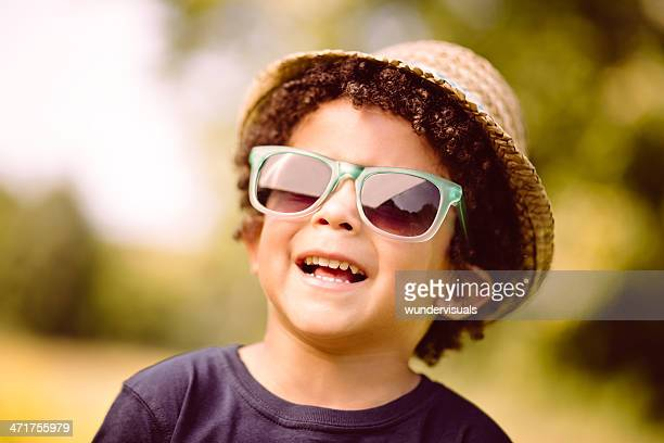 Little boy  with sunglasses smiling in nature