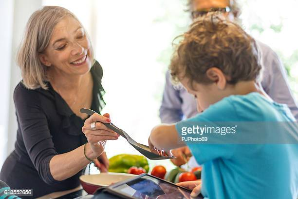 little boy with tablet is tasting food from grandmother - pjphoto69 fotografías e imágenes de stock