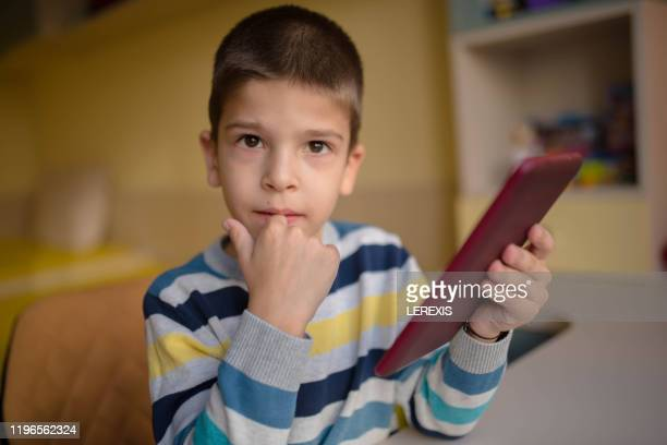 little boy with tablet looking at camera - lerexis stock pictures, royalty-free photos & images
