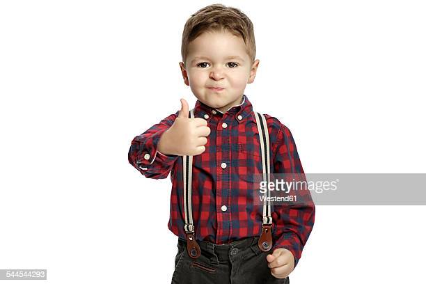 Little boy with thumb up wearing suspenders pouting mouth
