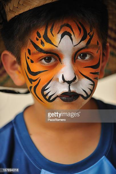Little boy with tiger mask painted on his face