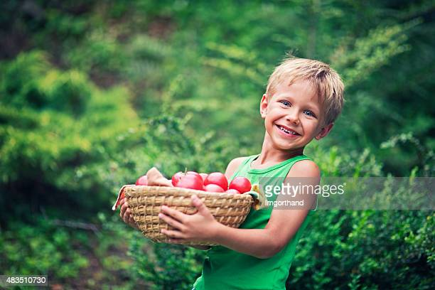 Little boy with tomatoes