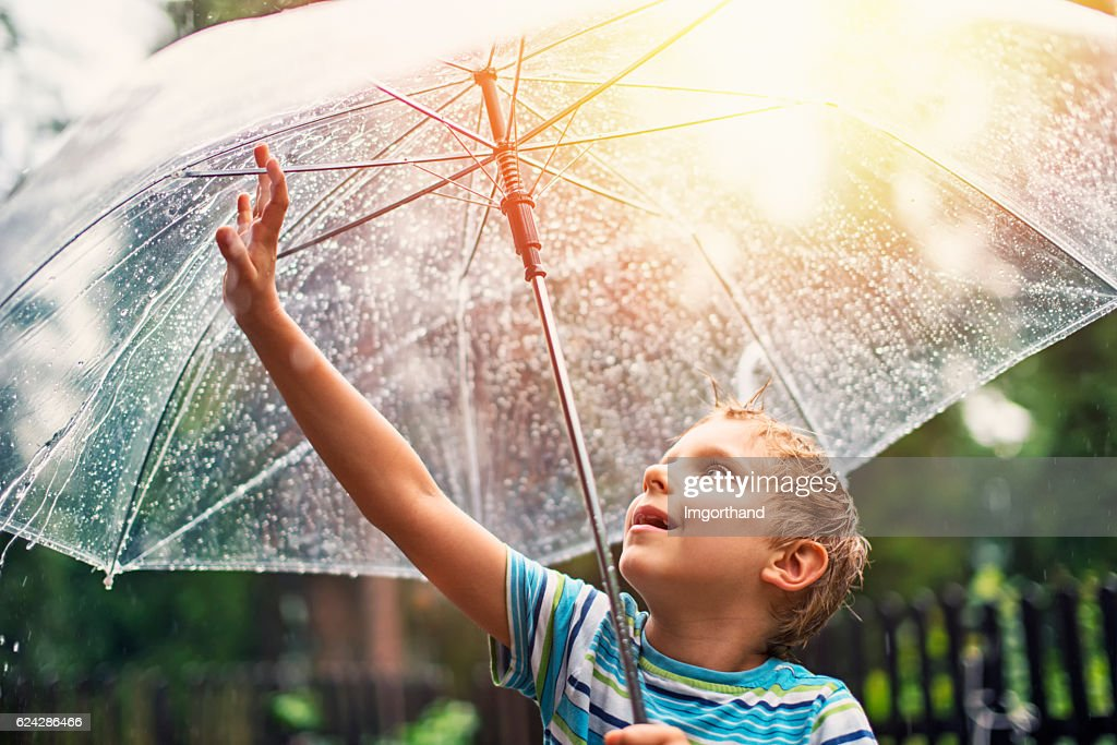 Little boy with transparent umbrella enjoying rain. : Stock Photo