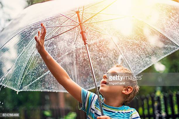 Little boy with transparent umbrella enjoying rain.