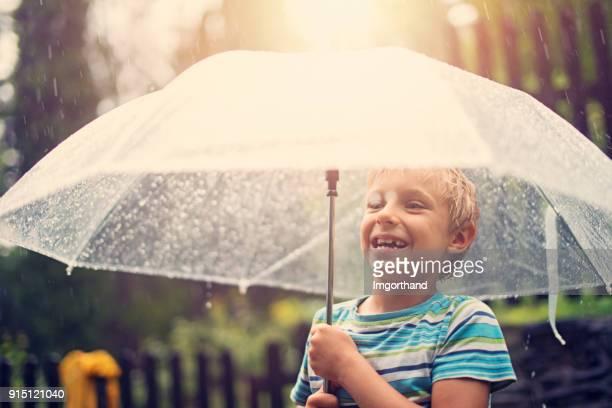 Little boy with transparent umbrella enjoying Spring rain.