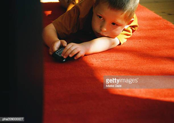 Little boy with TV controls.
