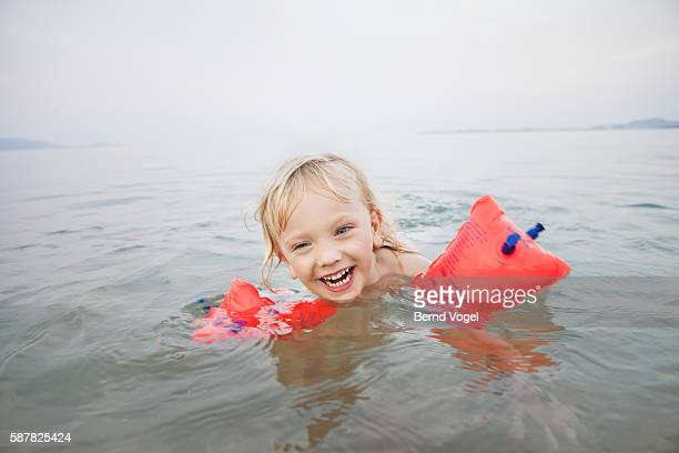Little boy (3-4) with water wings swimming 8a6c6fd6b55ac