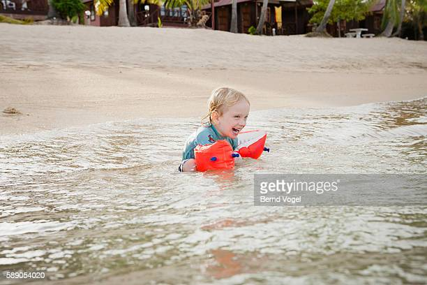 Little boy (3-4) with water wings swimming