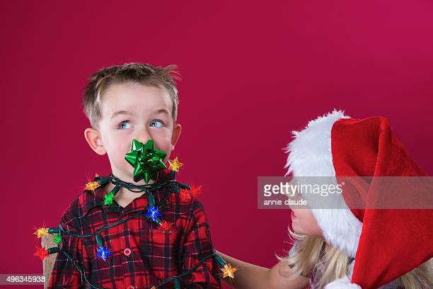 little boy wrapped in christmas lights - naughty santa stock photos and pictures