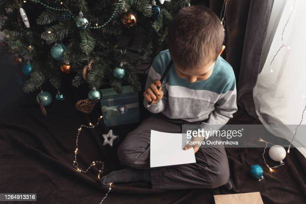 little boy write christmas wishes to santa - father christmas stock pictures, royalty-free photos & images