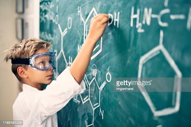 黒板に化学式を書く小さな男の子 - 発明家 ストックフォトと画像