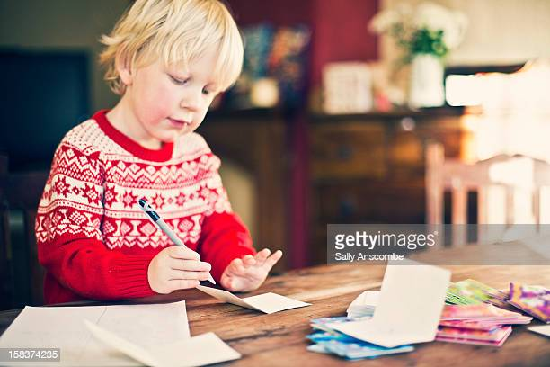 Little boy writing Christmas cards