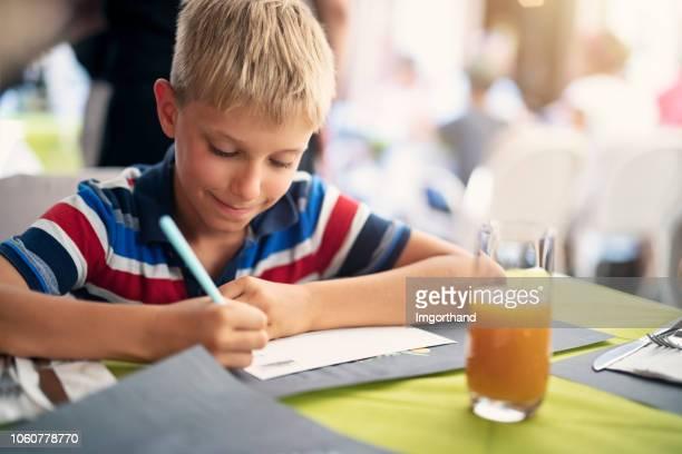 niño escribiendo postales en café de la calle - 8 9 años fotografías e imágenes de stock