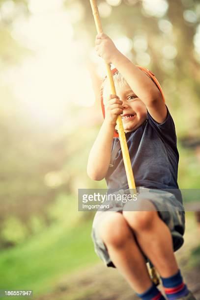 Little boy zipping in adventure park