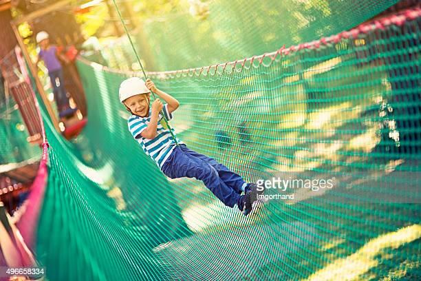 Little boy zipping en el parque de aventuras