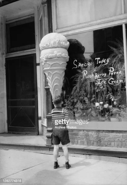 A little boys admires the enormous ice cream cone outside an ice cream parlour in Clarinda Iowa April 1936 The store is advertising today's special...