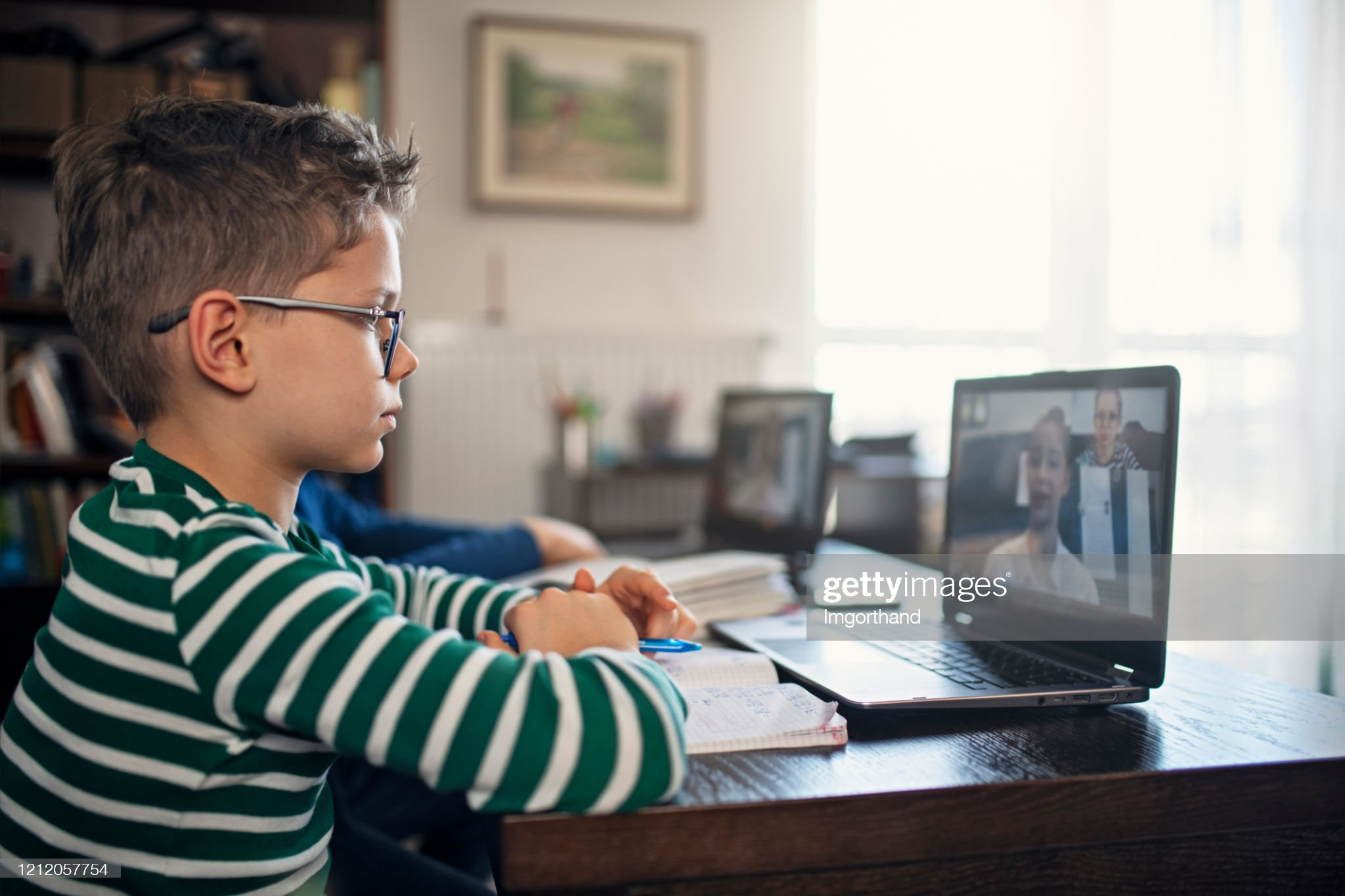 Little boys attending to online school class. : Foto stock