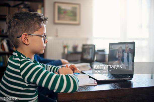 little boys attending to online school class. - distance learning stock pictures, royalty-free photos & images