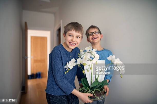 little boys carrying a flower for their mother - mother's day stock pictures, royalty-free photos & images