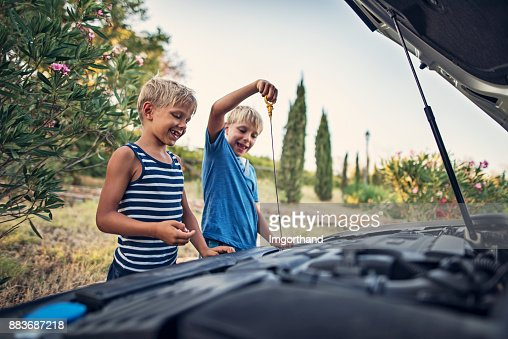 Little boys checking oil of family car