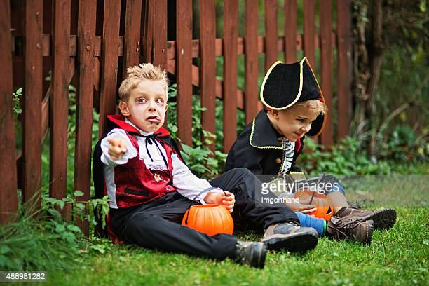 little boys during halloween sitting on grass and eating candy - funny skeleton stock photos and pictures