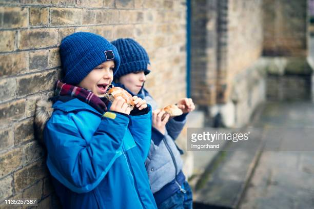 little boys eating traditional easter hot cross buns - hot cross bun stock pictures, royalty-free photos & images