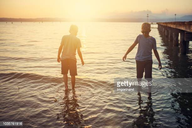 little boys enjoying sunset at garda lake, italy - wading stock pictures, royalty-free photos & images