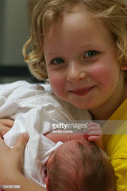 Little boy's first hold of his newborn baby sister