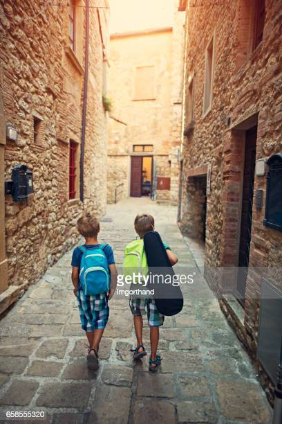 Little boys going to school in small italian town.
