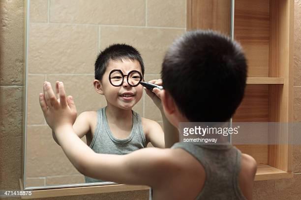 Kleine Junge ist graffiti im Badezimmerspiegel