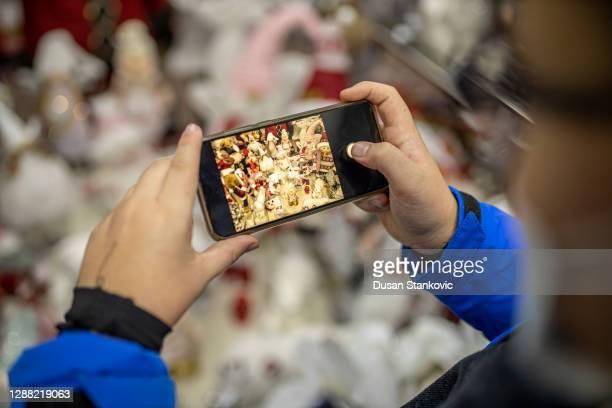 彼の携帯電話で新年の装飾の電話を取って小さな男の子の手 - モバイル撮影 ストックフォトと画像