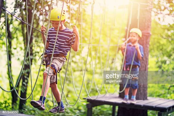 little boys having fun during in ropes course  adventure park - obstacle course stock photos and pictures
