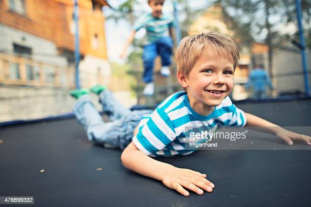 Little boys having fun on garden trampoline