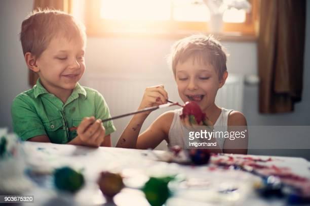 Little boys having fun painting easter eggs