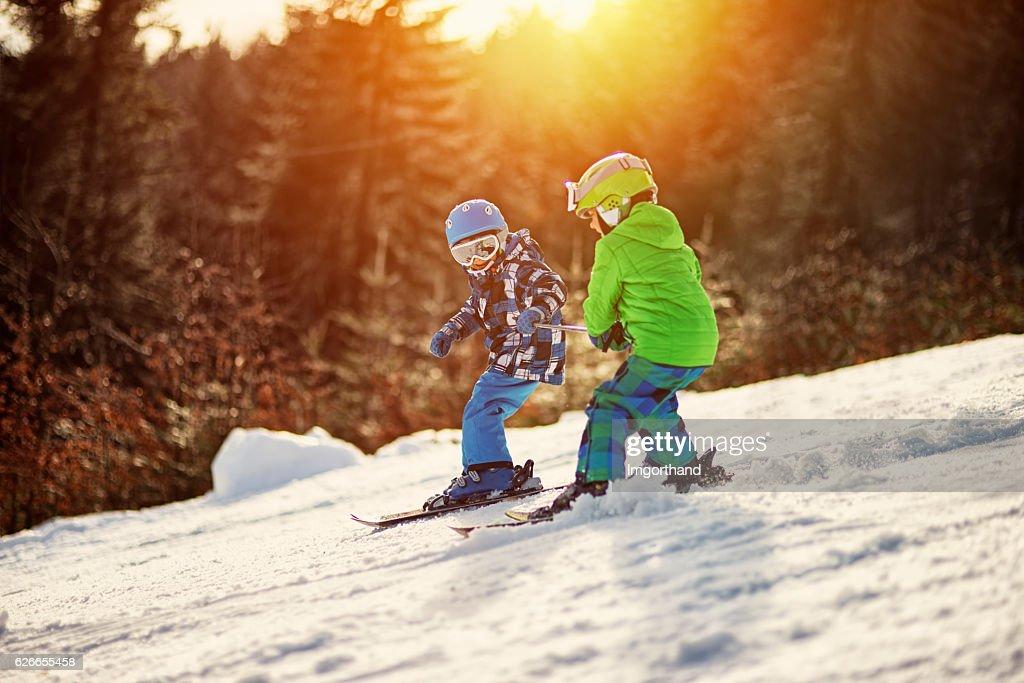 Little boys having fun skiing : Stock Photo