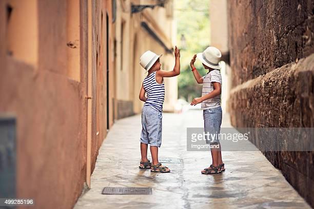 Petits garçons haute cinq dans une rue étroite