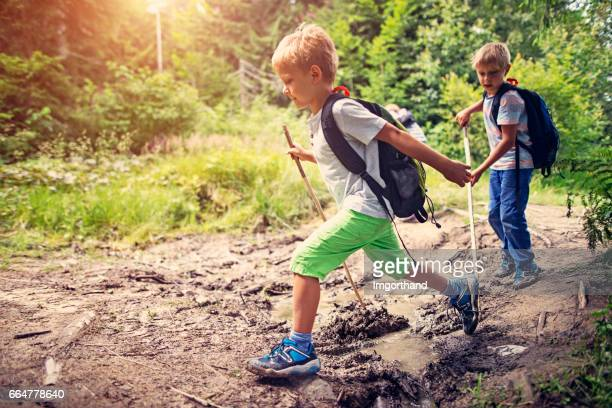 Little boys hiking on muddy path in forest