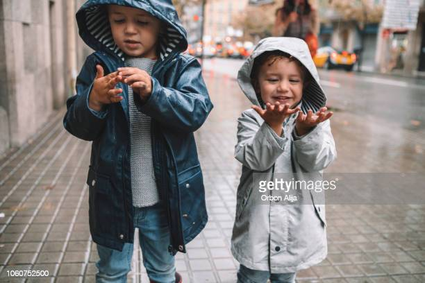 little boys in rain - coat stock pictures, royalty-free photos & images