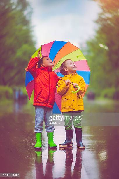 little boys in rain - multi colored coat stock photos and pictures